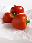 Three Red Cherry Peppers on White Paper