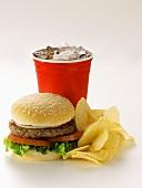 A Hamburger with Potato Chips and Soda