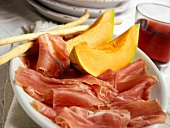 Sliced Proscuitto and Melon with Bread Sticks