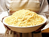 A Bowl of Spaghetti Being Held