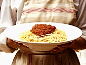 Bowl of Spaghetti with Meat Sauce; Being Held