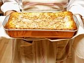 Woman Holding a Pan of Lasagna