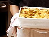 A Pan of Lasagna Being Held