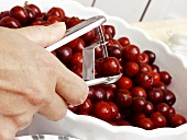 Cherries in a Bowl Being Pitted