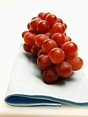 Bunch of Red Grapes Resting on a Blue Cloth