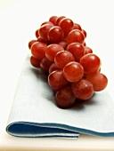 Rote Trauben auf blauem Tuch