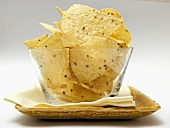 Tortilla Chips in a Glass Dish Resting on a Plate with Napkin
