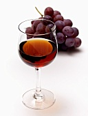 Glass of Red Wine with Red Grapes