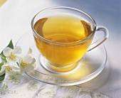 A cup of green tea, jasmine flowers beside it