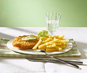 Escalope á la viennoise with lime slices, chips and a glass of water
