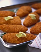 Breaded Fish on Baking Sheet with Lemon Lime Garnish