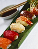 Assorted nigiri sushi on banana leaf