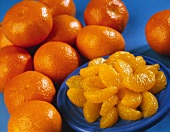 Blue Plate of Orange Segments with Whole Oranges
