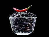 Black beans and red chilli in glass bowl