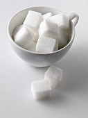 Sugar cubes in and beside white cup