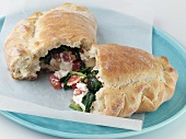 Spinach and Ricotta Calzone; Halved on Blue Plate