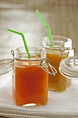 Carrot and orange juice and peach juice in preserving jars with straws