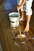 A man scrubbing a wooden floor with a broom