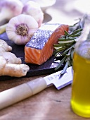 An arrangement of salmon, garlic, ginger, rosemary and olive oil