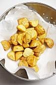 Fettgebackene Kartoffeln beim entfetten auf Küchenkrepp