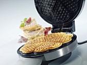 A waffle iron and a freshly baked waffle