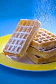 Sprinkling waffles with icing sugar