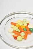 Vitamintabletten auf Glasteller