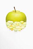 Vitamintabletten und Golden Delicious Apfel