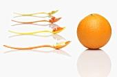 Löffel mit Vitamintabletten und eine Orange