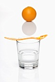 Vitamin tablets on a spoon on top of a glass of water with an orange in the background
