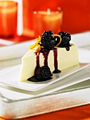 A piece of cheese cake with blackberry sauce