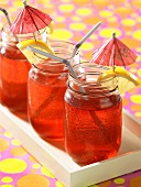 Red berry lemonade in jars with cocktail umbrellas