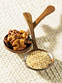 Roasted walnuts and sesame seeds on wooden spoons