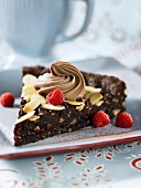 A slice of chocolate cake with slivered almonds and raspberries