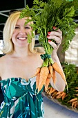 A woman holding a bunch of carrots at a market