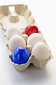 White and coloured eggs in an egg box