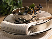 A festive place setting with a silver bowl