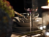 A festive place setting with a silver bowl and a wine glass