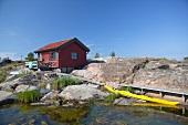 A wooden house and a canoe on a beach (Scandinavia)