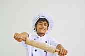 A boy dressed as a chef holding a rolling pin