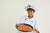 A boy dressed as a chef holding a pizza