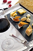 A tray of appitisers (cheese and jam) and a glass of red wine