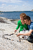 A couple making a heart out of stones on the beach