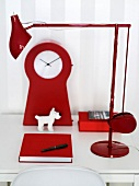 A white desk with a red lamp, clock, note book and a toy dog