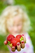 A blonde girl holding strawberries