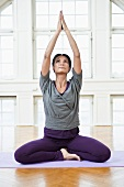 A woman practising yoga in a workout room