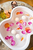 A rose petal bath with floating candles in a spa