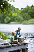 A father and son fishing by a lake