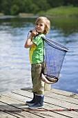 A little boy on a jetty holding a fishing net