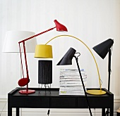 Various designer lamps and a stack of newspapers on a desk